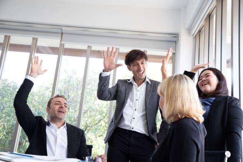 Los empresarios acertados y los hombres de negocios de lanzamiento combinan alcanzando metas que celebran dando arriba cinco en o fotografía de archivo libre de regalías