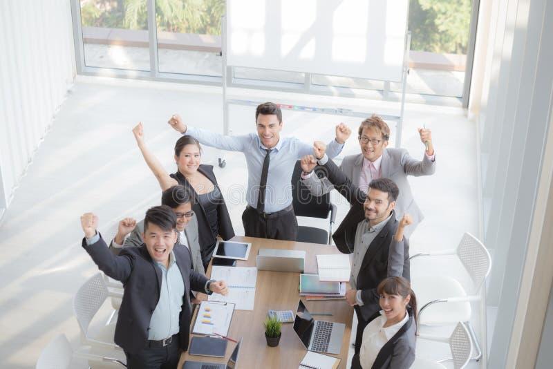 Los empresarios acertados y los hombres de negocios de lanzamiento combinan alcanzando metas que celebran un triunfo con los braz foto de archivo libre de regalías