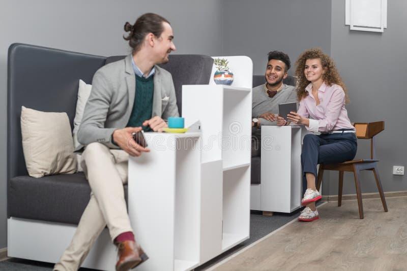 Los empresarios agrupan en el centro usando el teléfono elegante de la célula, encuentro de Coworking de la gente de la raza de l imagen de archivo libre de regalías