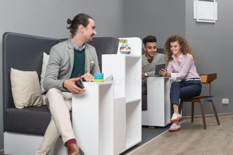 Los empresarios agrupan en el centro usando el teléfono elegante de la célula, encuentro de Coworking de la gente de la raza de l imagen de archivo