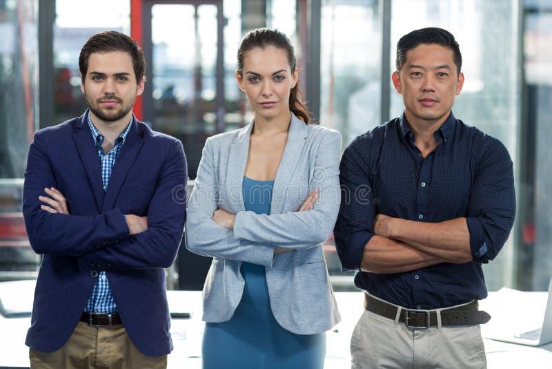Los empresarios confiados que se colocaban con los brazos cruzaron en oficina imagen de archivo