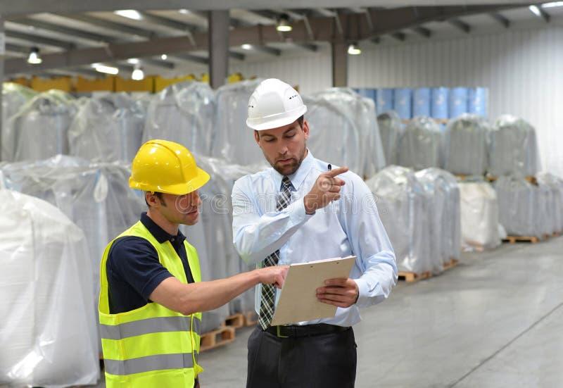 Los encargados y los trabajadores en la industria de la logística hablan del workin imagen de archivo libre de regalías