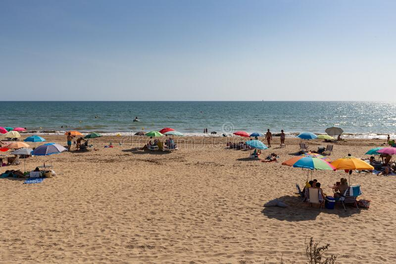Los Enebrales beach in Punta Umbria, Huelva, Andalusia, Europe. A sunny summer day on vacation with lots of people and blue sky stock photos