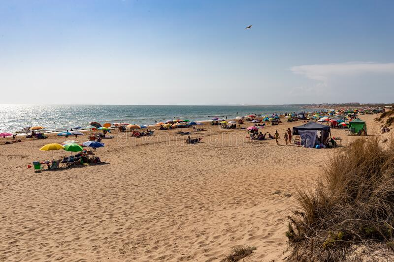 Los Enebrales beach in Punta Umbria, Huelva, Andalusia, Europe. A sunny summer day on vacation with lots of people and blue sky royalty free stock photography