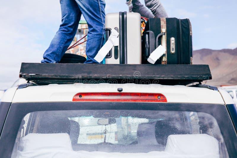 Los equipajes y los bolsos arreglaron en el tejado del coche listo para un viaje en fondo del cielo fotografía de archivo libre de regalías