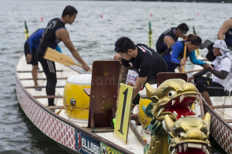Los equipos competentes de gente emprenden los barcos nativos de la cabeza del dragón de la fila de los deportes durante Dragon C imagen de archivo
