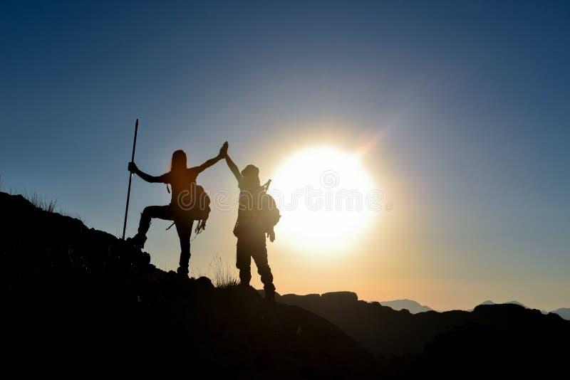 Los escaladores enarbolan imágenes de la felicidad y de la silueta imagen de archivo libre de regalías