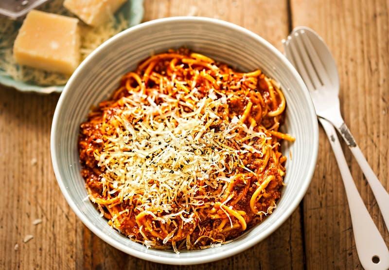 Los espaguetis boloñés con la carne de vaca picadita, salsa de tomate, rallaron el parmesano imagenes de archivo
