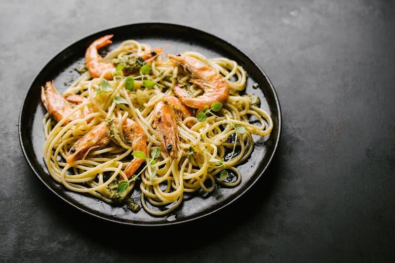 Los espaguetis con pesto y gambas sirvieron en la placa fotos de archivo