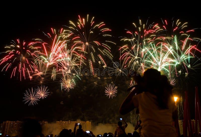 Los espectadores miran los fuegos artificiales hermosos en el cielo imagenes de archivo