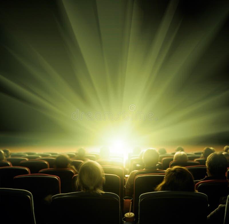 Los espectadores miran la luz brillante en el pasillo del cine imagenes de archivo