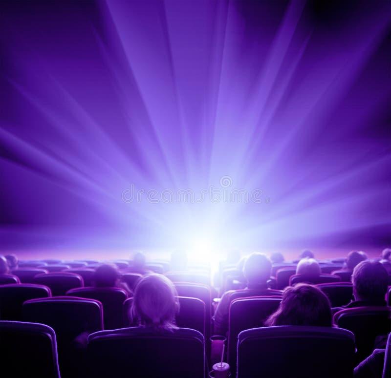 Los espectadores miran la luz brillante violeta en el pasillo del cine fotos de archivo