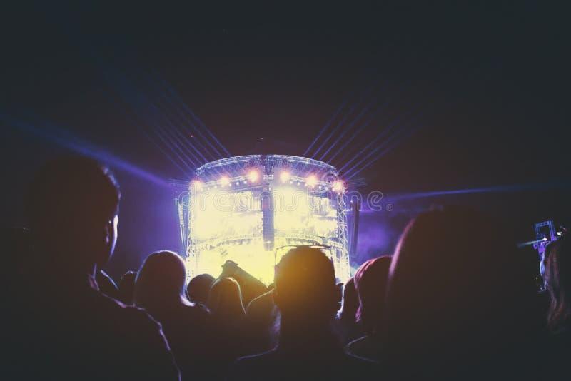 Los espectadores miran a una banda de rock realizarse en etapa fotos de archivo libres de regalías