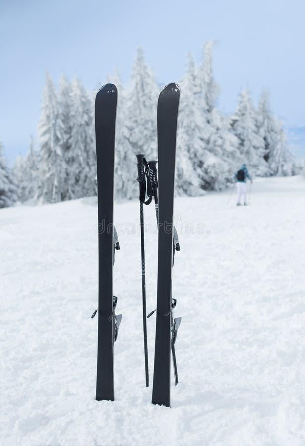 Los esquís y los palillos se pegaron en nieve en pico de montaña foto de archivo
