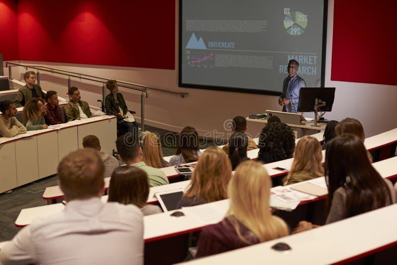 Los estudiantes adultos jovenes en una universidad dan una conferencia, visión trasera imagenes de archivo