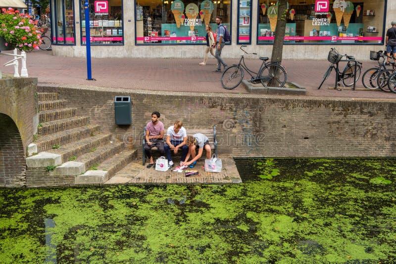 Los estudiantes almuerzan el sushi en el canal en la cerámica de Delft, Países Bajos fotografía de archivo
