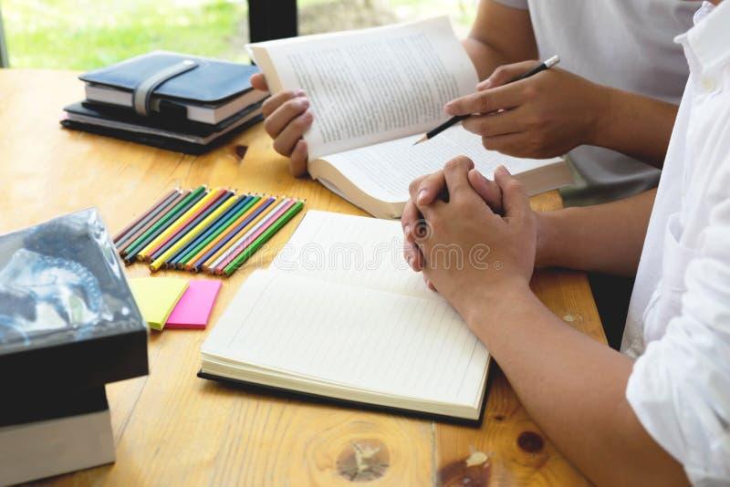 Los estudiantes ayudan al amigo que enseña y que aprende a adicional sujeto en biblioteca Concepto de la educación imagen de archivo