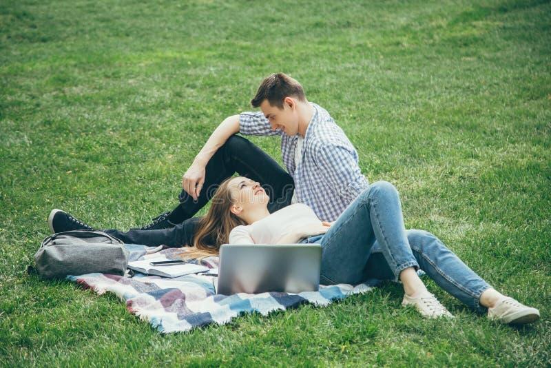 Los estudiantes cariñosos de los pares se relajan después de escuela en el césped foto de archivo libre de regalías