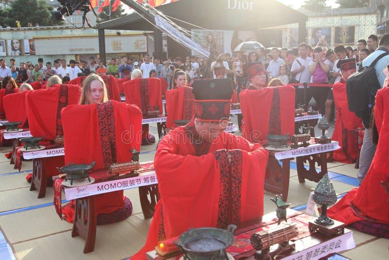 Los estudiantes chinos y extranjeros con una bendición del hanfu recolectaron en la torre de reloj en la ceremonia imagen de archivo libre de regalías