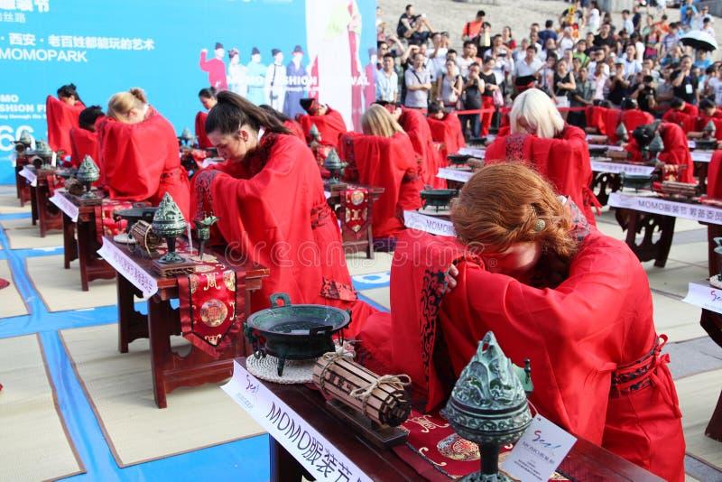 Los estudiantes chinos y extranjeros con una bendición del hanfu recolectaron en la torre de reloj en la ceremonia fotos de archivo