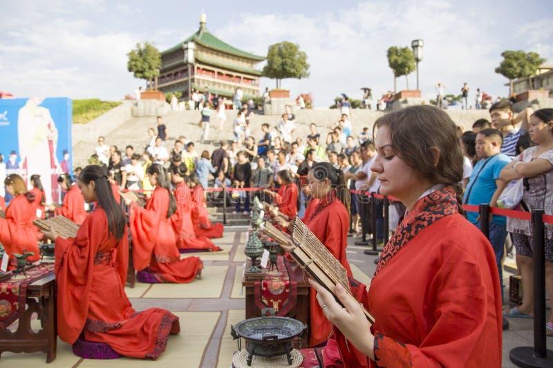 Los estudiantes chinos y extranjeros con una bendición del hanfu recolectaron en la torre de reloj en la ceremonia imagen de archivo