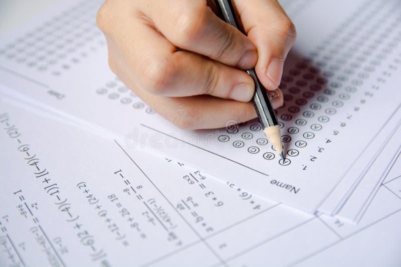 Los estudiantes dan llevar a cabo la opci?n seleccionada escritura del l?piz en las hojas de las hojas de respuesta y de pregunta imagen de archivo