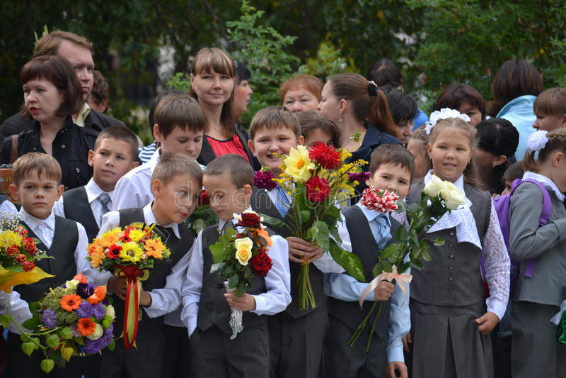 Los estudiantes de la escuela se colocan con las flores en manos el 1 de septiembre. imagenes de archivo