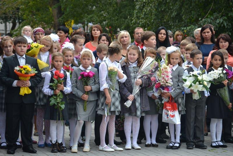 Los estudiantes de la escuela se colocan con las flores en manos el 1 de septiembre. imagen de archivo