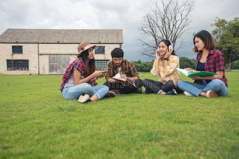 Los estudiantes del grupo sonríen y se divierten y escuchan la música él también h imagen de archivo