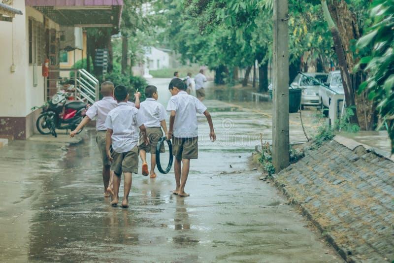 Los estudiantes del muchacho salen de la sala de clase para caminar en la calle despu?s de fuertes lluvias fotografía de archivo