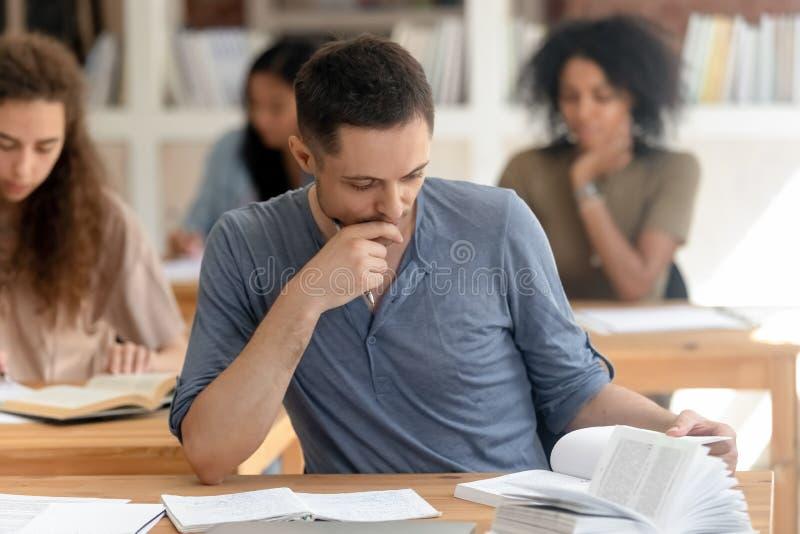 Los estudiantes diversos absorbieron el libro de texto de la lectura que estudiaban sentarse en los escritorios foto de archivo
