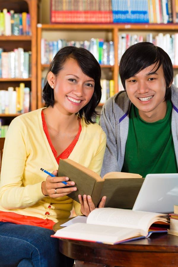 Los estudiantes en biblioteca son un grupo de aprendizaje imágenes de archivo libres de regalías