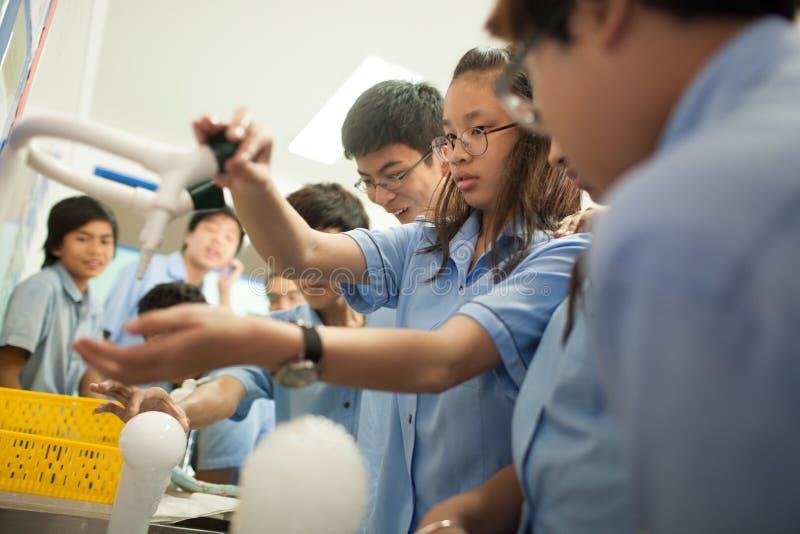 Los estudiantes en ciencia clasifican, estudiando la reacción del hielo seco fotografía de archivo