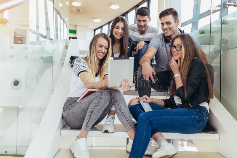 Los estudiantes est?n estudiando en biblioteca La gente joven est? pasando el tiempo junto Libro de lectura y rato de comunicaci? fotografía de archivo
