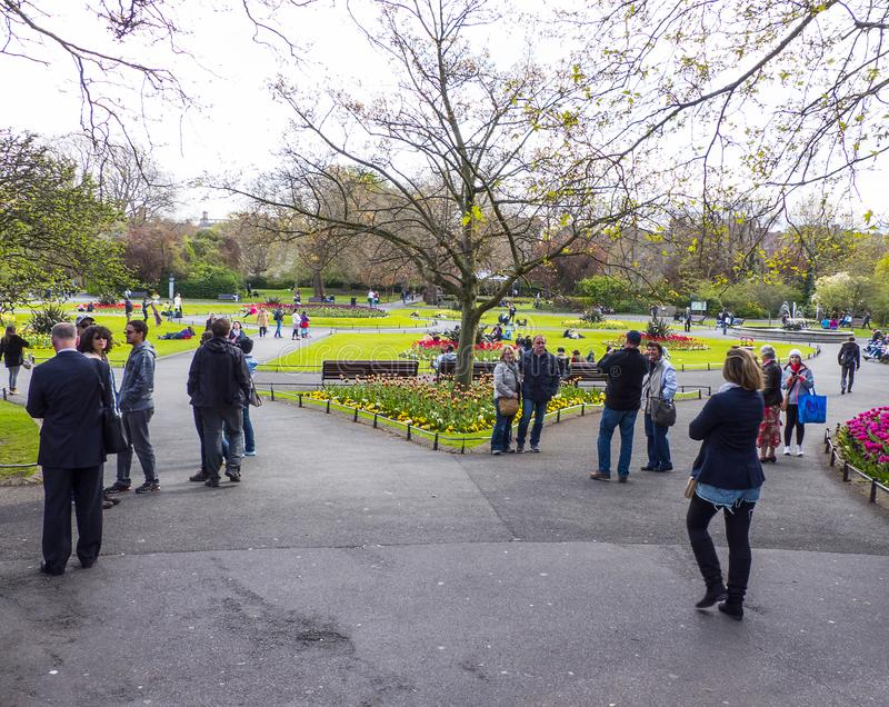 Los estudiantes, los hombres de negocios y los turistas dan un paseo y charlan en el parque de Phoenix en Dublín en una tarde bri imágenes de archivo libres de regalías
