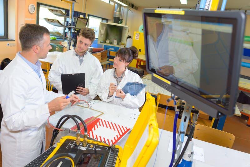 Los estudiantes jovenes que trabajan en ciencia proyectan juntos en laboratorio fotografía de archivo
