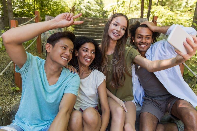 Los estudiantes multiétnicos felices de los amigos al aire libre hacen el selfie fotografía de archivo libre de regalías