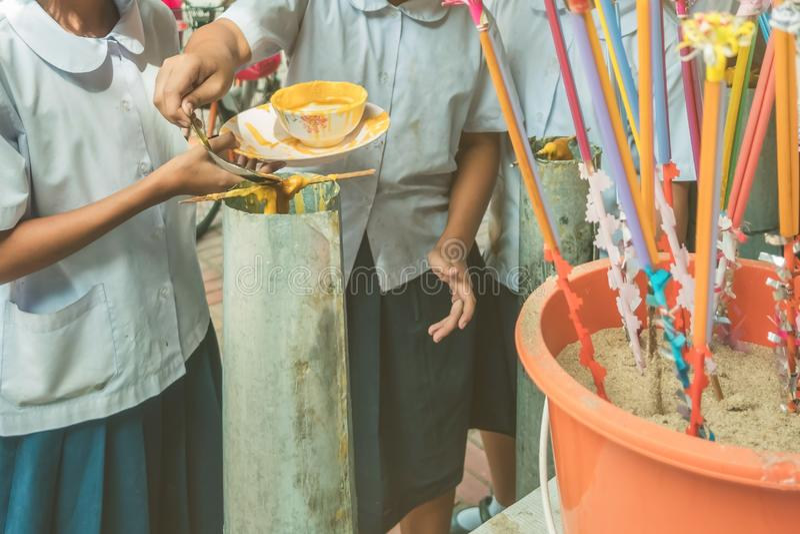 Los estudiantes se unen a oferta echada de fusión de la vela al templo para Lent Day budista, imagen de archivo libre de regalías