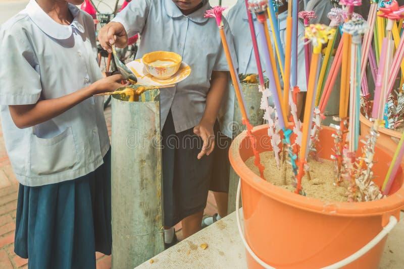 Los estudiantes se unen a oferta echada de fusión de la vela al templo para Lent Day budista, fotografía de archivo