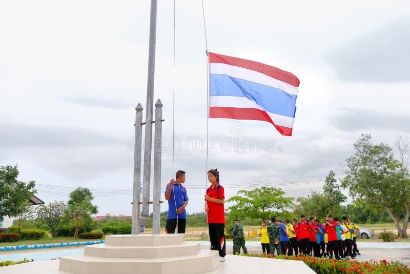 Los estudiantes tailandeses están subiendo la bandera nacional tailandesa al top de th foto de archivo libre de regalías