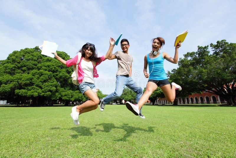 Los estudiantes universitarios felices saltan imagen de archivo
