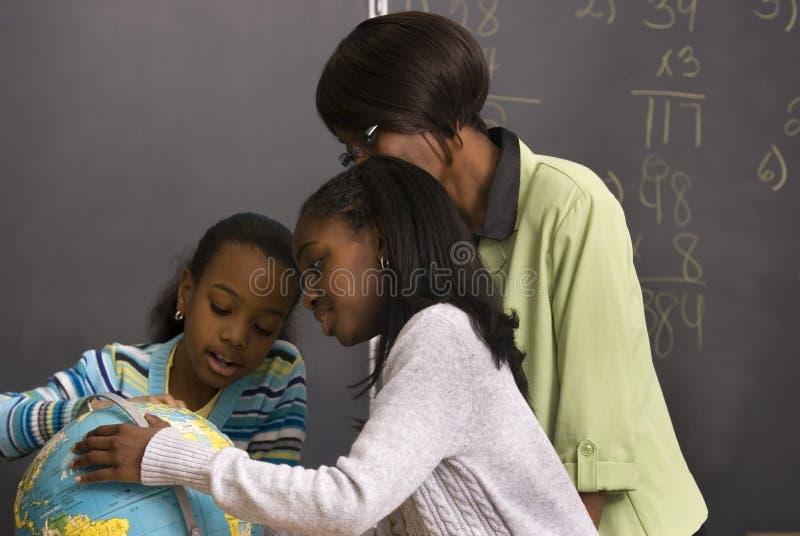 Los estudiantes y el profesor buscan el globo en la clase imagen de archivo