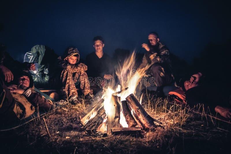 Los exploradores del grupo de personas que descansan por el fuego en aire libre acampan después de día que camina largo en la noc fotografía de archivo libre de regalías