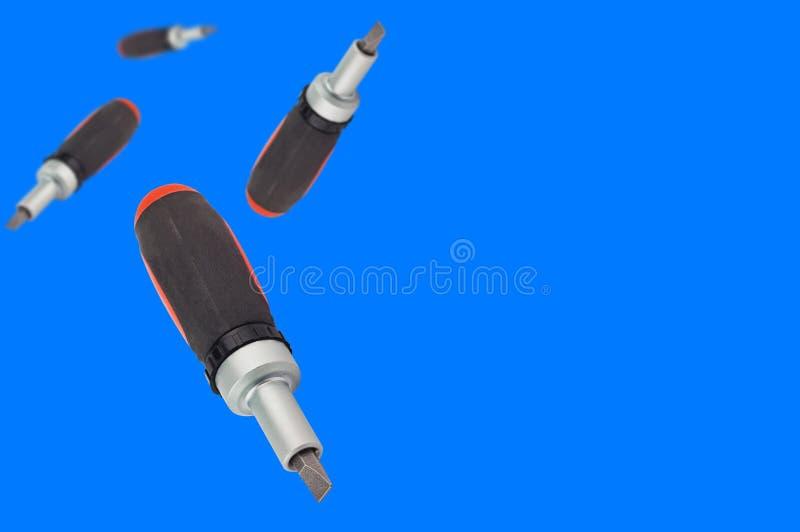 Los fallender Ratschenschraubenzieher mit orange und schwarzem Plastik mit Gummigriff und St?ckchen auf blauem Hintergrund mit Ko stockfotografie