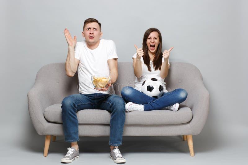 Los fanáticos del fútbol de griterío chocados del hombre de la mujer de los pares animan para arriba el equipo preferido de la ay imagen de archivo libre de regalías