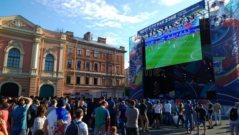 Los fanáticos del fútbol en la zona de la fan de la ciudad de St Petersburg miran el partido en la pantalla grande fotografía de archivo