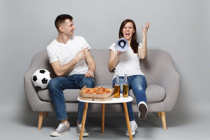 Los fanáticos del fútbol enojados del hombre de la mujer de los pares animan para arriba el equipo preferido de la ayuda, grito e foto de archivo libre de regalías