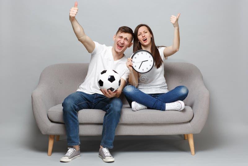 Los fanáticos del fútbol del hombre de la mujer de los pares de la diversión animan encima del equipo preferido de la ayuda con e foto de archivo libre de regalías