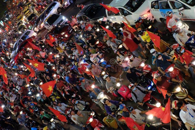 Los fanáticos del fútbol vietnamitas de la descripción celebran triunfo en las calles en la noche imagenes de archivo