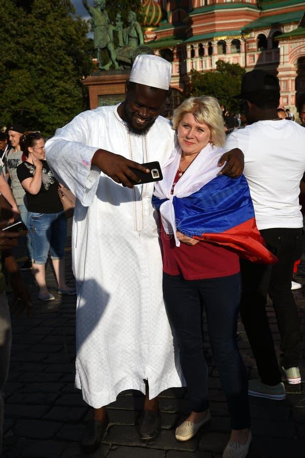 Los fan?ticos del f?tbol presentan para las fotos en la Plaza Roja en Mosc? foto de archivo